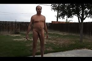 A stripped old man peeing uppish back patio.
